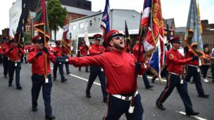 A flag bearer sings and stretches his arms out as he marches in a parade