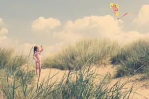 A girl stands on sand dunes holding a brightly coloured kite