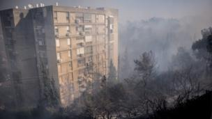 Smoke rises from a fire that has erupted in a suburb of the coastal city of Haifa