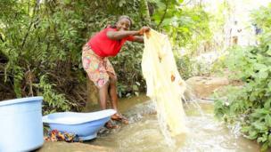 Mujer lavando ropa en un riachuelo
