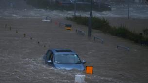 A car is stranded in seawater as high waves hit the shore during Typhoon Mangkhut at Heng Fa Chuen in Hong Kong, China on 16 September 2018.