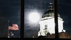 The moon appears bright white between a United States of America flag and the Indiana capitol building