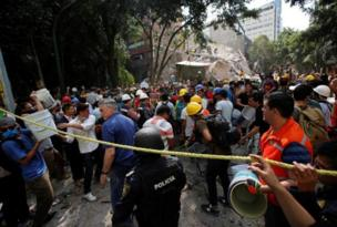 People wey dey stay for Mexico city use bucket to help remove rubble from one collapsed building.
