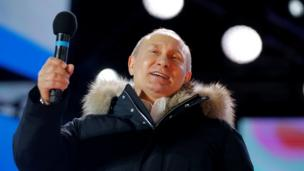 """Russian President and Presidential candidate Vladimir Putin delivers a speech during a rally and concert marking the fourth anniversary of Russia""""s annexation of the Crimea region, at Manezhnaya Square in central Moscow, Russia March 18, 2018."""