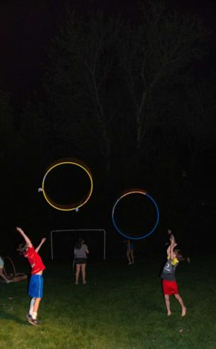 Children throw hula hoops into the air at night in the garden