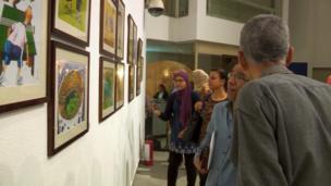 زوار المعرض أمام لوحات