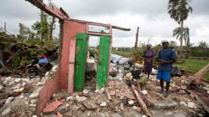 Saintanor Dutervil stands with his wife in the ruins of their home destroyed by Hurricane Matthew in Les Cayes, Haiti