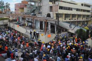 Crowds of volunteers and parents join rescue effort wey dey go on for Enrique Rébsamen elementary school wen collapse for Coapa, South-east of di capital, wey be Mexico City.