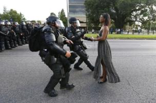 A woman stands in front of riot police