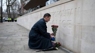 A member of the public lays flowers outside New Scotland Yard