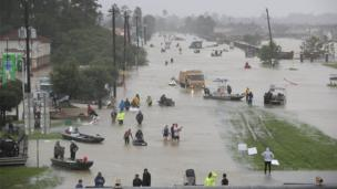 Image shows a flooded street in Houston with rescue boats and people wading through knee-deep water.