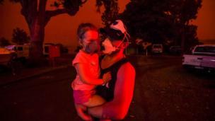 Um morador de Mallacoota segura sua filha com máscaras na fumaça.