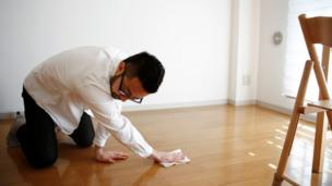 Minimalist Fumio Sasaki uses a wet wipe to clean the floor in his room in Tokyo