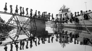 Filas de hombres transportando hacia un barco cestos llenos de carbón en sus cabezas. Las filas se ven reflejadas en el agua.