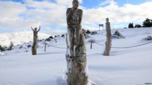 ग्रीस की राजधानी एथेंस में 'द पार्क ऑफ़ सोल' में लगी खुली प्रदर्शनी में लकड़ी से बनी एक प्रतिमा और उसके आसपास ज़मीन पर बिछी बर्फ़ की ख़ूबसूरत चादर.