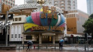 Pedestrians walk past Casino Lisboa in Macau which has closed because of Typhoon Mangkhut on 16 September 2018