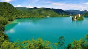 A very still and turquoise lake is hugged by green trees all around it