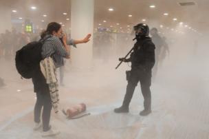 Una mujer le habla a un policía en El Prat