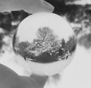 Un panorama de invierno reflejado en una bola de metal.