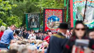 Spectators watch bands and Royal Black Institution members carrying banners on parade in Scarva