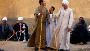 رجلان يقفان بتحدي قبل تأدية رقصة التحطيب