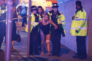 Police officers help an injured woman leave the Manchester Arena