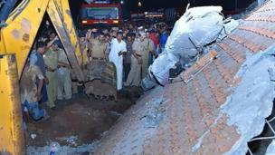 Indian officials and bystanders gather beside a collapsed building after an explosion and fire at The Puttingal Devi Temple in Paravur
