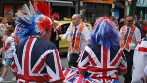 Women dressed in union jacks watching the Twelfth of July parade