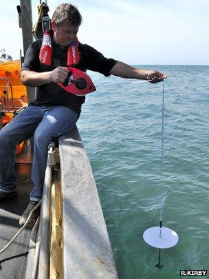 Skipper Alan Steer taking a secchi disk measurement (Image: Richard Kirby)