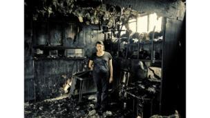 Mujer en medio de su hogar luego de un incendio.