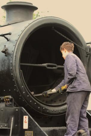 Joven limpiando una locomotora