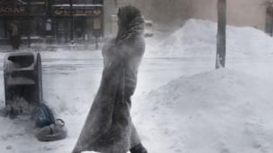 seorang pria melawan dingin dengan menggunakan selimut