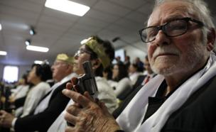 A man holds a pistol during a ceremony at the World Peace and Unification Sanctuary