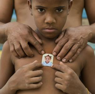A child holds a photograph of themselves up to their chest.