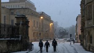 Three police officers walking through the snow in Oxford