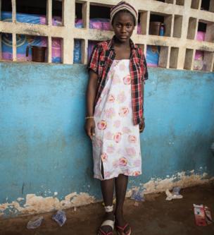 مبالو بانغوار تقف في مدرسة الحي وتلف ضمادا على كاحلها الأيمن الذي تأذى أثناء هروبها من الفيضانات