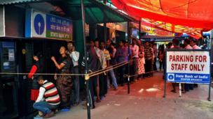 गुवाहाटी में स्टेट बैंक के बाहर पैसे निकालने और जमा करने के लिए लगी लोगों की लंबी कतार