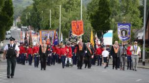 A group of marchers carry flags and banners in a parade as a police officer walks ahead