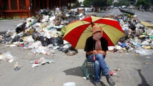 متظاهر يحمل شمسية ويجلس أمام أكوام من القمامة