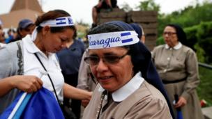 Nuns are seen wearing headbands in the country's national colours