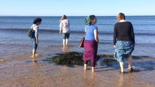 Women standing in shallow sea water