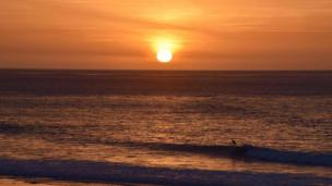 The sun rises over Langland Bay, Swansea, as a surfer takes to the water. Picture by Mark de'Boer Lloyd