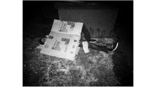 Hombre durmiendo en la calle tapándose con una caja de cartón.