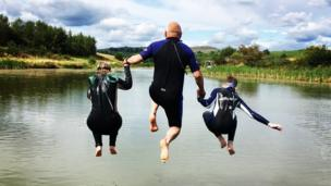 Family jump in a lake at Hundred House near Builth Wells, Powys