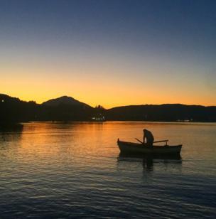 A fisherman sails on a calm sea as the sun sets