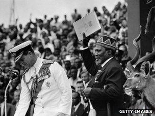 Jomo Kenyatta (right) holds official document of independence, December 1963
