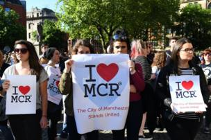 People attend a vigil for the people who lost their lives during the Manchester terror attack.