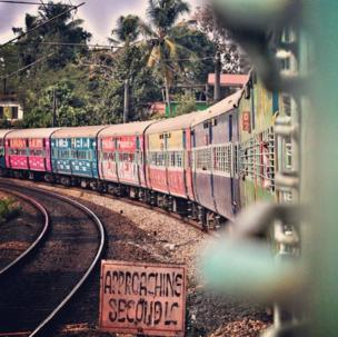 A train with brightly coloured coaches.