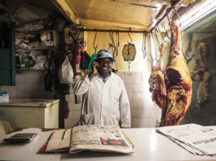 Kenya, 2014. A butcher uses his mobile phone.
