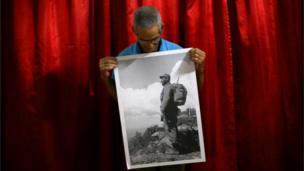 Ramon Anecio Gonzalez Gil poses with a photograph of Fidel Castro in Coliseo, Cuba, November 29, 2016.